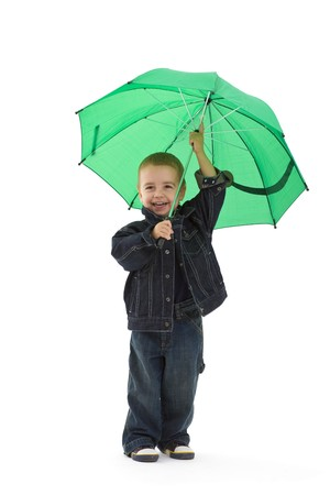Young boy wearing jeans jacket, holding green umbrella. Isolated on white background. Stock Photo - 7284091