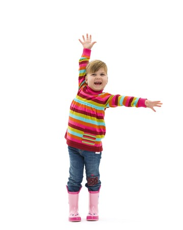 Happy little girl in colorful sweater, jeans and pink boots, laughing and waving. Isolated on white background. photo