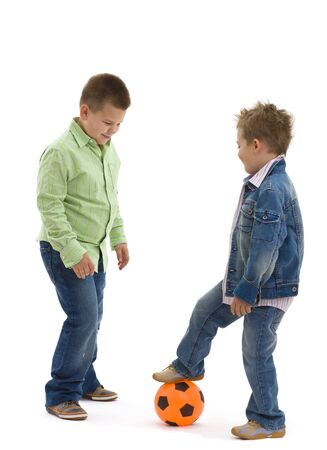 boys playing: Young brothers wearing trendy jeans clothers, playing football, on isolated white background. Stock Photo