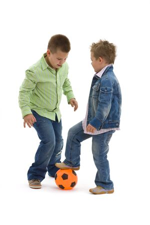 wear: Young brothers wearing trendy jeans clothers, playing football, on isolated white background. Stock Photo