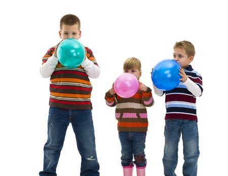 3 children wearing trendy, colorful clothes blowing up toy balloons. Isolated on white background. photo