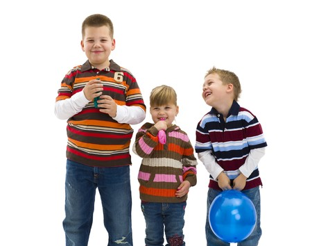 Happy children wearing trendy, colorful clothes holding toy balloons, laughing. Isolated on white background. photo