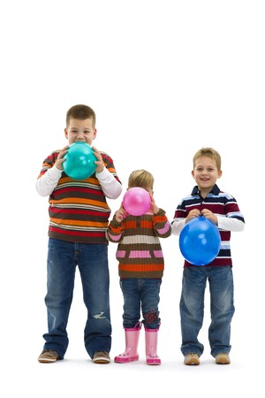 3 happy children wearing jeans and colorful striped t-shirts, blowing up toy balloons. Isolated on white background. photo