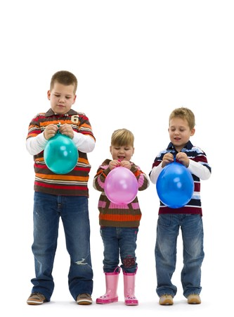 Happy children wearing jeans and striped t-shirt, holding colorful toy balloons, laughing. Isolated on white background. photo
