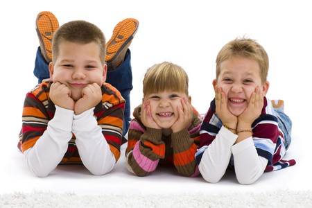 family photo: Group of 3 happy children lying on floor, wearing colorful, striped pullover and t-shirt, smiling.  Isolated on white background.