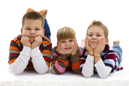 Group of 3 happy children lying on floor, wearing  colorful, striped pullover and t-shirt, laughing.  Isolated on white background. photo