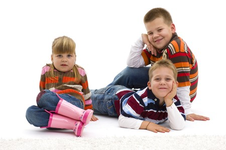 Group of 3 happy children lying on floor wearing colorful, trendy clothes, smiling. Isolated on white background. photo