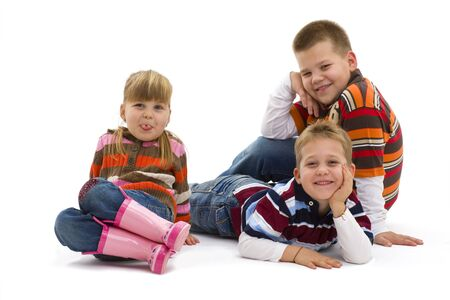 Group of 3 happy children lying on floor wearing colorful, trendy clothes, smiling. Isolated on white background. Stock Photo - 7284125