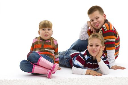 Group of 3 happy children lying on floor wearing colorful, trendy clothes, sticking their toungues out. Isolated on white background. photo