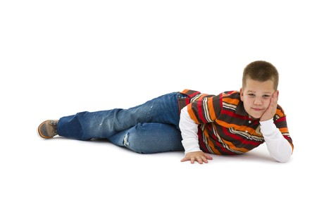 Boy wearing trendy colorful t-shirt, lying on floor, leaning on hand, smiling. Isolated on white background. photo