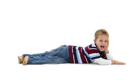 トレンディなカラフルな t シャツを着て、床に横たわって、笑いの若い男の子。白い背景で隔離されました。