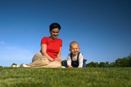 Baby and his mother are having outdoor fun together and they are smiling a lot. There are nice afternoon lights. photo