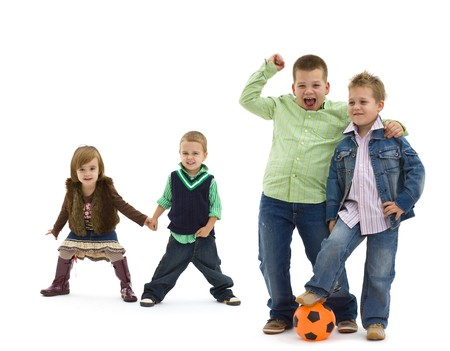 Group of 4 happy children posing together.  laughing and waving. Two boys with football in the forground, two small kids holding hands in the background. Isolated on white. photo