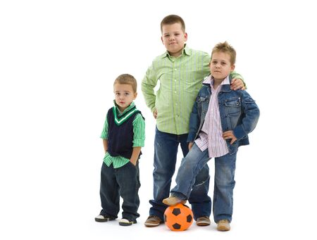 Young boys wearing trendy jeans clothes posing togethers with football, on isolated white background. photo