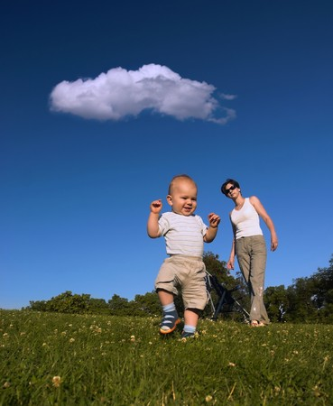 weekends: 10 months old baby is doing his fist little steps while his mother is watching him. Stock Photo