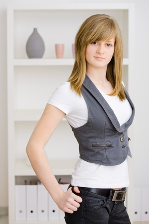 Teen girl standing with hands on hip at home, wearing jeans vest and white t-shirt. photo
