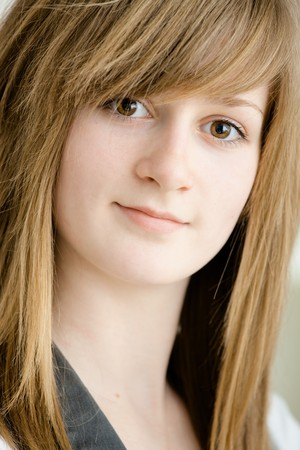 Closeup portrait of teenage girl with long blond hair and big brown eyes, smiling. Stock Photo - 7347781