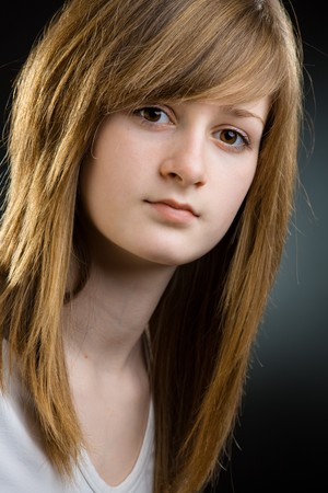 Closeup portrait of pretty teenage girl with long blond hair and big brown eyes, smiling. Stock Photo - 7347798