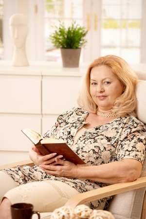 Elderly woman sitting in living room, reading book in armchair, smiling. Stock Photo - 7347780