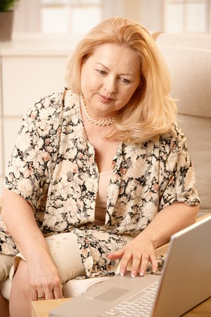 Senior woman working with laptop computer with small smile, typing. photo