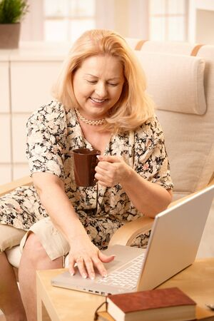 Senior woman drinking coffee, looking at laptop computer with big smile, typing. photo