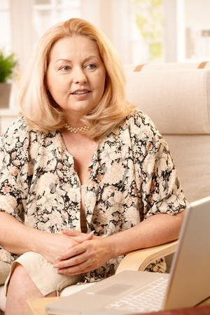 Senior woman sitting at home with laptop computer. Stock Photo - 7347788
