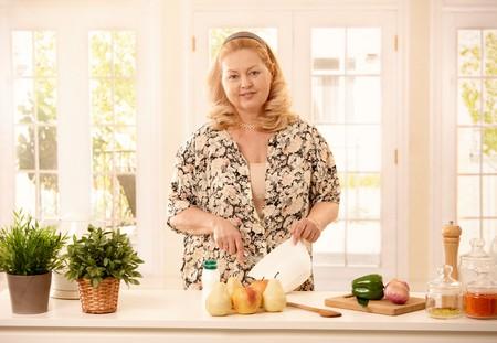 whisking: Mature blonde woman smiling at camera standing in kitchen, cooking, whisking egg. Stock Photo