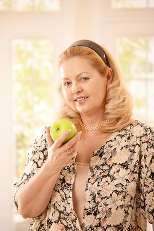 Portrait of senior blonde woman holding green apple smiling at camera. photo
