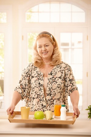 Senior woman holding a tray with diet food, orange juice, fruit, tea and yogurt. photo