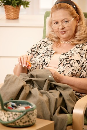 Senior woman sitting in armchair sewing a shirt, using sewing kit. Stock Photo - 7347786