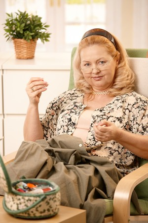 Portrait of mature blonde woman looking at camera, smiling, sewing a shirt at home. Stock Photo - 7347787