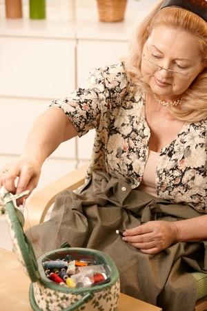Smiling senior woman sitting in armchair, opening sewing kit. Stock Photo - 7347797