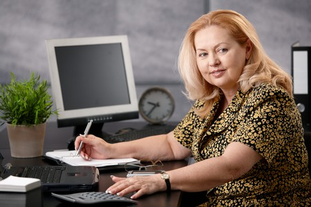 Senior woman sitting at office desk working, writing notes to personal organizer, smiling. Stock Photo - 7347794