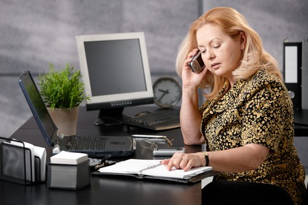 Senior woman sitting at office desk talking on mobile phone matching dates from personal organizer. photo