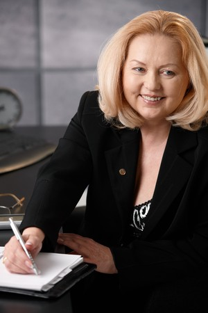 Smiling senior businesswoman taking note, looking at calendar sitting at office desk. photo