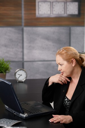 Senior businesswoman working on computer, typing on keyboard, looking at screen, smiling in office. photo