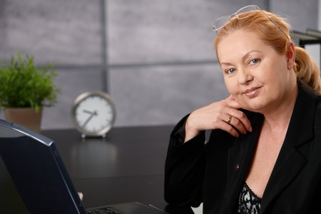 wise woman: Portrait of senior executive businesswoman sitting at desk in office, looking at camera.