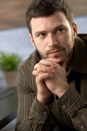 Serious young man looking determined sitting with hands folded. Stock Photo - 7347779