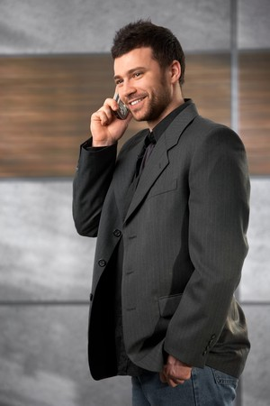 Trendy young businessman talking on mobile phone in office lobby, smiling. photo