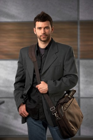 Handsome trendy office worker standing in lobby holding laptop bag looking at camera confidently. photo