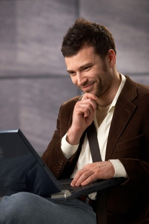 Happy guy wearing stylish clothes using laptop computer, smiling. photo