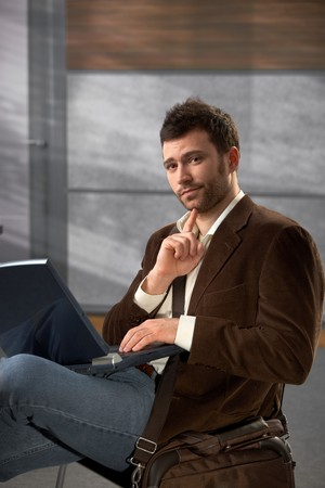 Portrait of goodlooking trendy man sitting on office lobby using laptop computer, looking at camera. photo