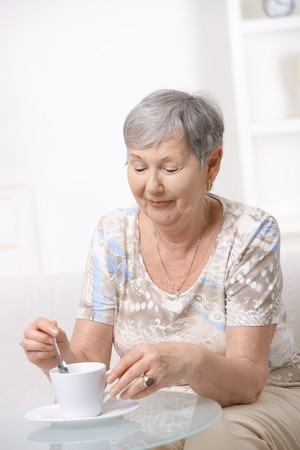 Senior woman sitting at coffee table, drinking coffee. photo
