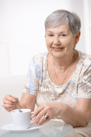 Happy senior woman sitting at table, drinking coffee, smiling. photo