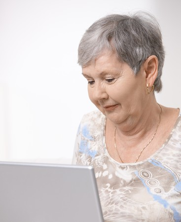 Portrait of senior woman using laptop computer, looking at screen. Stock Photo - 7347665