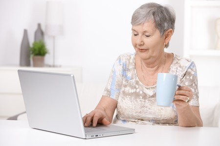 tea cosy: Senior woman sitting at desk using laptop computer, looking at screen. Stock Photo