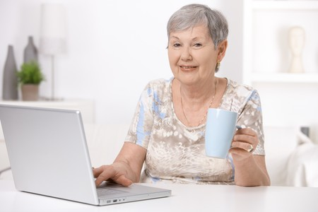 Senior woman sitting at desk using laptop computer, drinking tea.