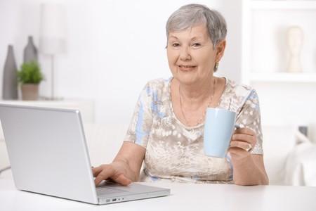 only one senior: Senior woman sitting at desk using laptop computer, drinking tea.