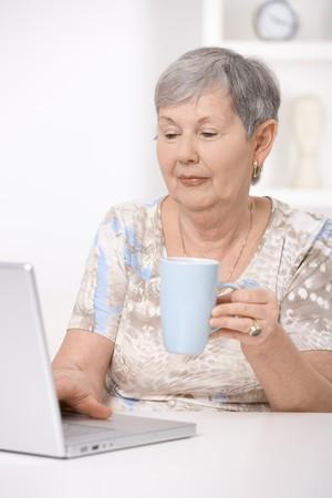 Senior woman browsing internet at home, using laptop computer. photo