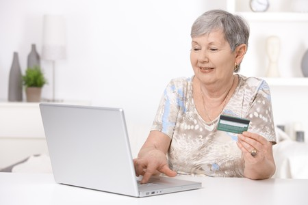 tea cosy: Senior woman shopping on internet, paying with credit card. Stock Photo